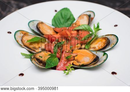 Mussels In Pink Sauce With White Wine On A White Plate