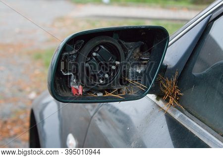 Broken Rearview Mirror Of Car Wreck.old Car Wreck Parked By The Garage. Someone Looted It And Remove