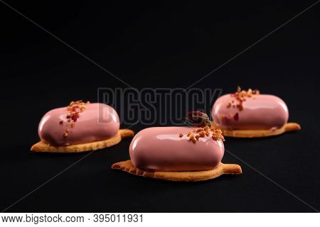 Pink Cakes Decorated With Nuts And Dry Rose Flower Isolated On Black Background. Dessert With Smooth