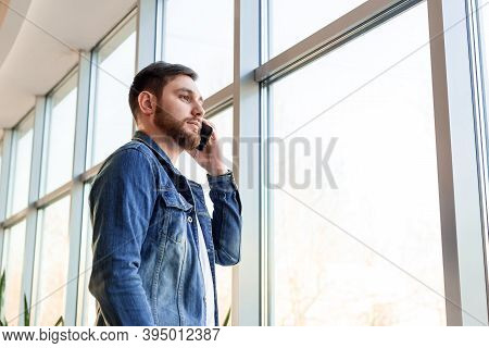 Young Man Making Business Call Talking By Phone Indoors Near Window Wall In Casual Jean Jacket. Smar