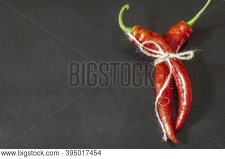 Two Pods Of Ripe Red Chili Peppers On Black Background. Freshly Plucked From Vegetable Patch And Tie