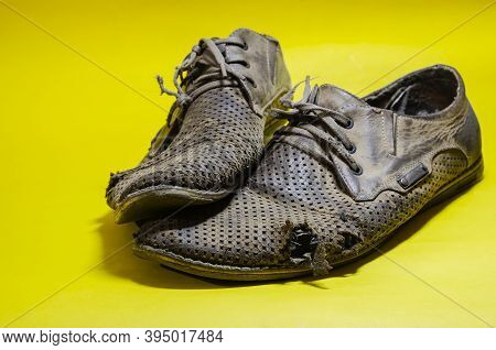 Old Torn Yellow Summer Shoes On A Yellow Background. A Pair Of Men's Heavily Worn Leather Shoes.