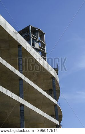 Geometric Shape Made Of Concrete On A Background Of Blue Sky. Unfinished Building Of A Modern Shoppi
