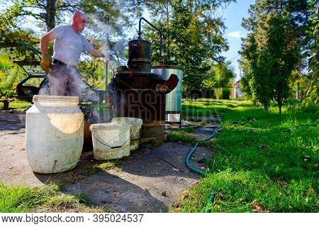 Man Is Unloading Boiler Of Homemade Distillery Made Of Copper To Release Used Fruit Marc, Making Moo