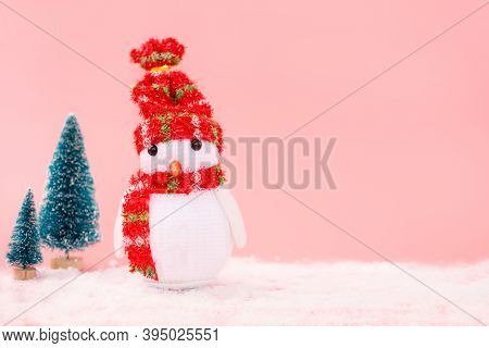 Amigurumi Snowman With Small Christmas Trees On A Pink Pastel Background. Christmas Greeting Card Co