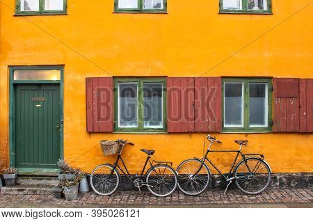 Bicycles In Front Of An Yellow Orange House Facade In Nyboder, Historic Row House District Of Former