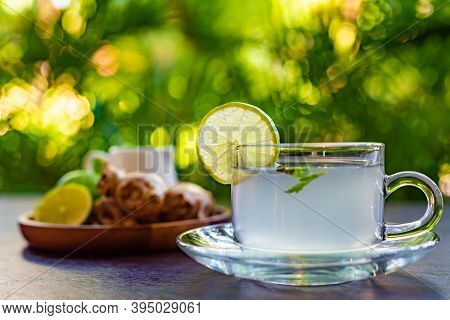 Side View, Ginger Tea With A Slice Of Lime And Mint Leaves, A Wooden Plate With Ginger Root And Whol