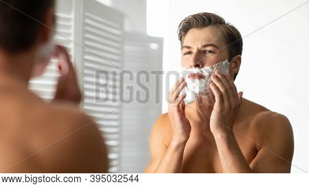 Male Facial Skincare And Selfcare Routine Concept. Confident Shirtless Handsome Man Applying Shave F