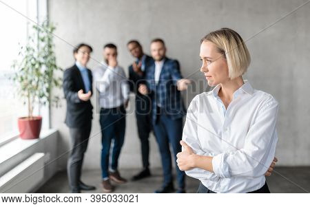 Sexism And Bullying At Work. Unhappy Victimized Business Lady Standing While Her Male Coworkers Whis