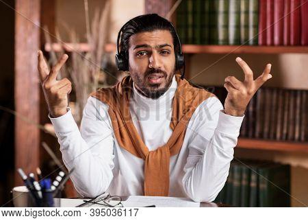 Online Teaching. Young Male Teacher In Headphones Talking To Camera Tutoring Explaining Lesson Remot