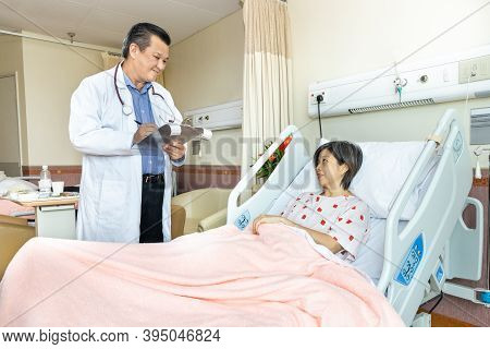 Confident Asian Medical Doctor Explaning To Cheerful Female Patient On Medical Condition Lying On Be