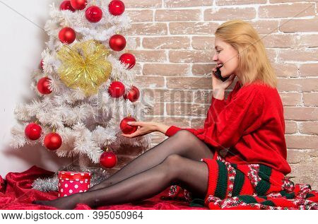 Woman Cheerful Hold Smartphone Enjoy Mobile Phone Conversation. Girl Sit Near Christmas Tree. Waitin