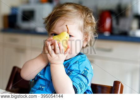 Cute Adorable Toddler Girl Eating Fresh Pear . Hungry Happy Baby Child Of One Year Holding Fruit.