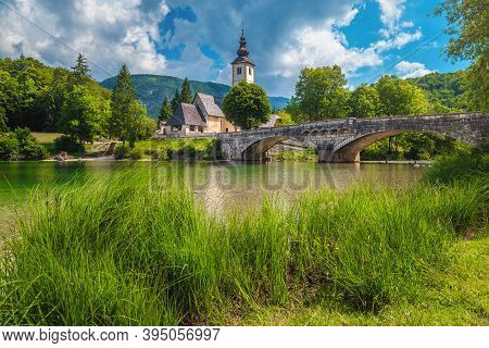Beautiful Summer Scenery And Travel Location With Famous Alpine Church On The Shore Of Lake Bohinj,