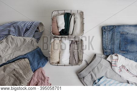 A Group Of Organic Cotton Clothing Set On A White Table Is Ready To Be Folded Into White Baskets.the