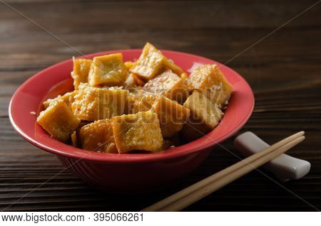 Crispy Deep Stir Fried Tofu Cubes In Clay Dish On Wooden Kitchen Table