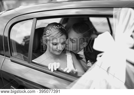 Black And White Photo Of Wedding Couple In Car. Wife And Husband Enjoy Moment Of Happiness. Portrait