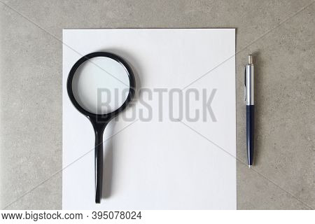 Template Of White Paper With A Ballpoint Pen, Magnifying Glass And On Light Grey Concrete Background
