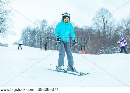 Young Adult Smiling Woman Skiing Down By Hill