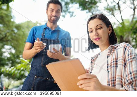 Beautiful Young Woman Reading Menu On Tablet Computer When Smilng Ewaiter Taking Notes In Notepad