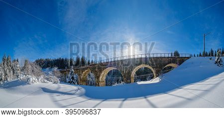 Stone Viaduct (arch Bridge) On Railway Through Mountain Snowy Fir Forest. Snow Drifts On Wayside And
