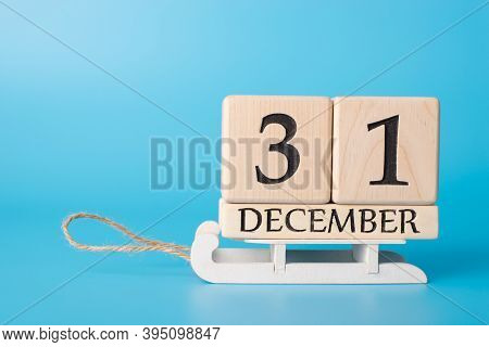 Close Up Photo Of Wooden Cube Calendar Showing The Last Day Of Old Year Standing On Little White Woo