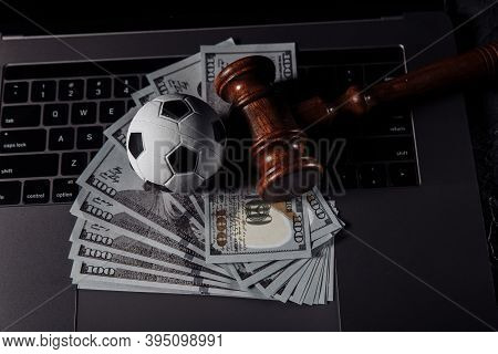 Soccer Ball And Wooden Gavel On Laptops Keyboard. Corruption In Sports Or Betting Concept