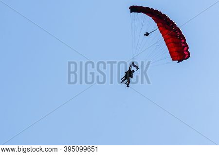 Tandem Parachute Jump. Silhouette Of Skydiver Flying In Blue Clear Sky