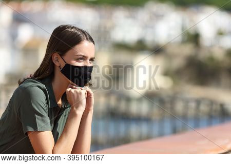 Happy Woman Wearing Mask Avoiding Coronavirus Contagion Contemplating Views On Vacation From A Balco