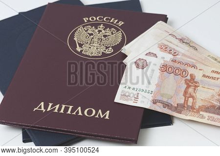 Diploma Of Higher Education Of Russia On A White Background And Cash Notes, The Inscription In Russi