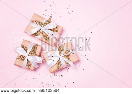 Christmas Composition Greeting Card. Gifts From Craft Paper On A Pink Background With A Gold Star Co