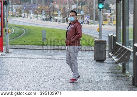 11/16/2020. Prague. Czech Republic. A Man Wearing A Mask Is Waiting For A Tram At Hradcanska Tram St