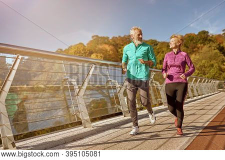 Stay In Shape. Full Length Shot Of Active Mature Family Couple In Sportswear Smiling At Each Other W