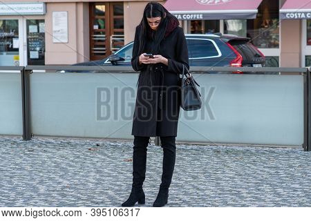 11/16/2020. Czech Republic. A Woman Wearing A Mask Is Waiting For A Tram At Hradcanska Tram Stop Dur