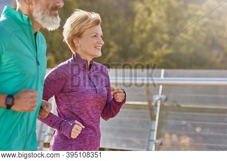 In Motion. Cheerful Active Mature Woman In Sportswear Smiling While Running On A Sunny Day. Joyful S