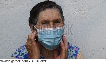 Elderly Woman Touches Mask By Hands. Old Lady Wears Face Mask To Protect From Viruses And To Prevent