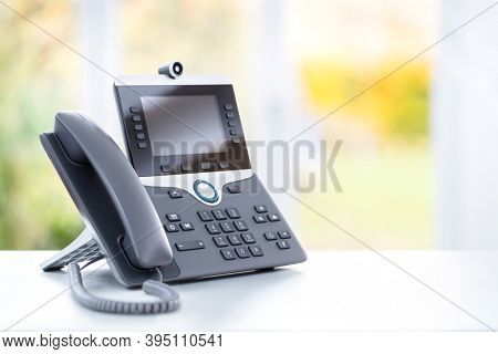 Business voip telephone with liquid crystal display and camera on a desk in an office