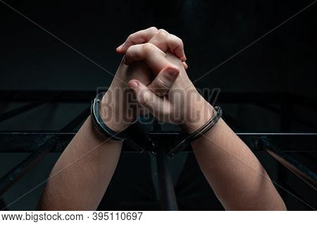 Hands Of Prisoner With Handcuff In Jail As Background, Hands In Handcuffs Behind Bars, Man In The Ha