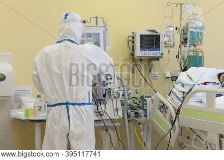 Male Nurse With Protective Coverall Clothing In Intensive Care Unit In Hospital.  Dialysis Machine,
