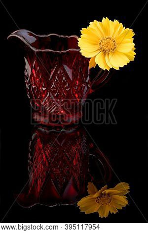 An Heirloom Cut Crystal Little Red Jug With A Yellow Daisy On The Handle Against A Black Background