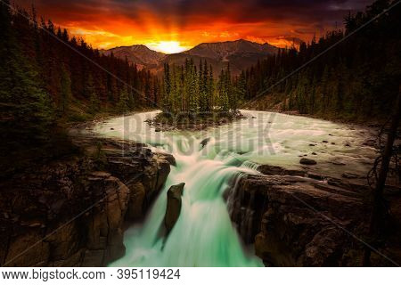Glacier River And Waterfall Flowing In The Beautiful Canadian Rockies. Dramatic Colorful Sunset Sky