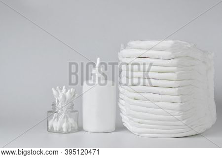 Baby Diapers And Diaper Rash Powder And Cotton Swabs On A White Background. There Is Space For Text.