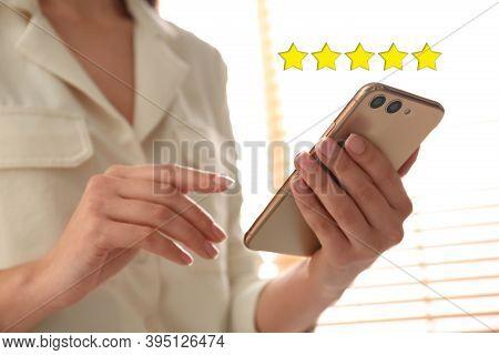 Woman Leaving Review Online Via Smartphone Indoors, Closeup. Five Stars Over Gadget
