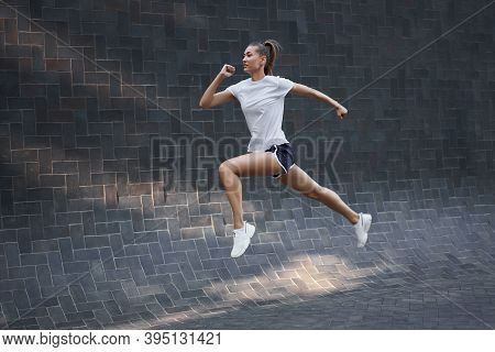Woman With Fit Body Jumping And Running Against Black Wall Background. Female Model In Sportswear Ex