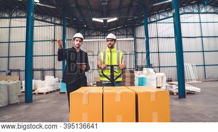 Factory Workers Deliver Boxes Package On A Pushing Trolley In The Warehouse . Industry Supply Chain