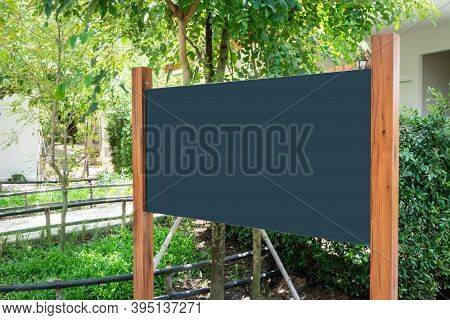 Black Board Mockup With Wood Poles Structure Against Nature Background.