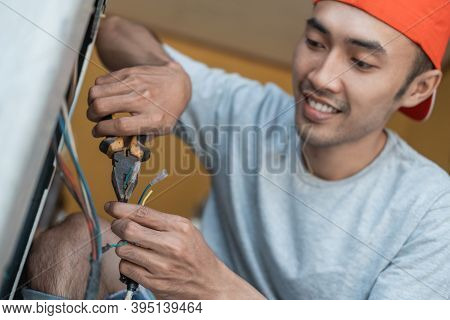 Close Up Of An Asian Electronics Worker Using Pliers To Fix A Washing Machine Cable That Broke