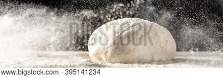 Yeast Dough For Bread Or Pizza On A Floured Surface, With Flour Splash. Cooking Bread. Kneading The