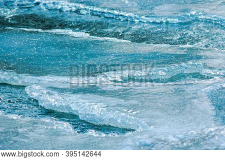 Ice Texture On The River. Close Up Background. Blue Color In Day Light. Water Flow Among Cracks