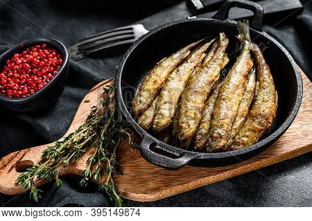 Whole Fried Battered Capelin Fish Served On A Metal Skillet. Black Background. Top View